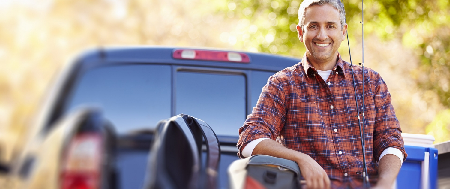 Portrait Of Man Sitting In Pick Up Truck On Camping Holiday